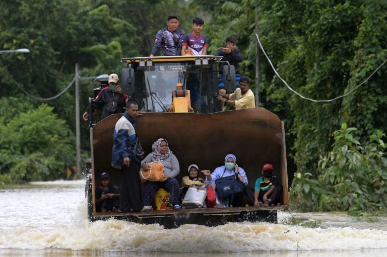 Residents ride a digger through floodwaters following heavy monsoon downpours in Lanchang in Malaysia's Pahang state