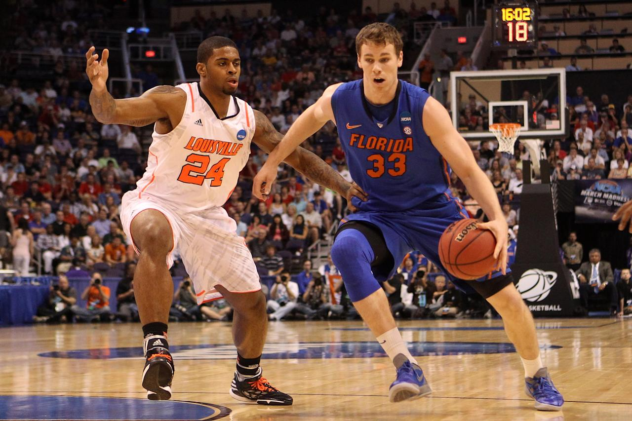 PHOENIX, AZ - MARCH 24:  Erik Murphy #33 of the Florida Gators drives on Chane Behanan #24 of the Louisville Cardinals in the first half during the 2012 NCAA Men's Basketball West Regional Final at US Airways Center on March 24, 2012 in Phoenix, Arizona.  (Photo by Christian Petersen/Getty Images)