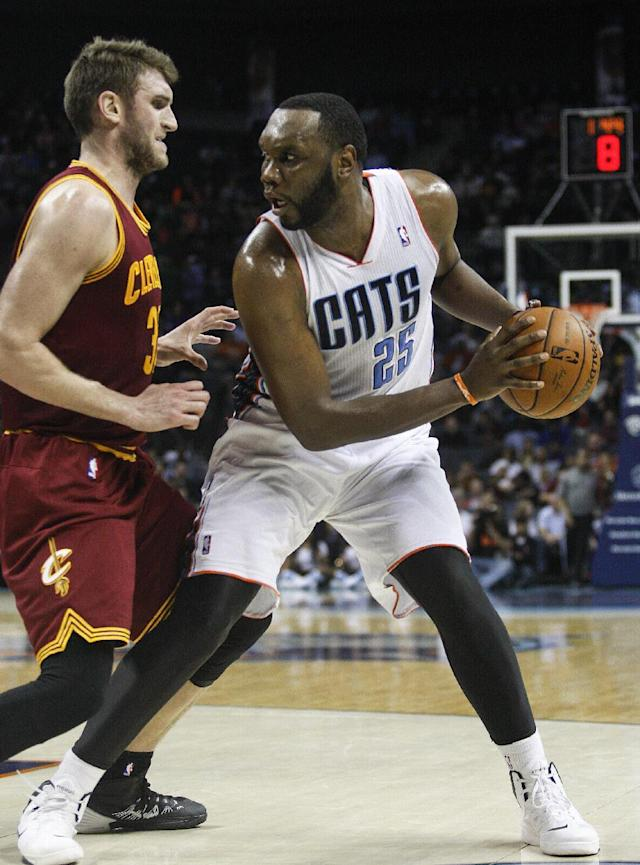 Charlotte Bobcats center Al Jefferson, right, looks to pass against Cleveland Cavaliers center Spencer Hawes during the second half of an NBA basketball game in Charlotte, N.C., Friday, March 7, 2014. Charlotte won 101-92. (AP Photo/Nell Redmond)