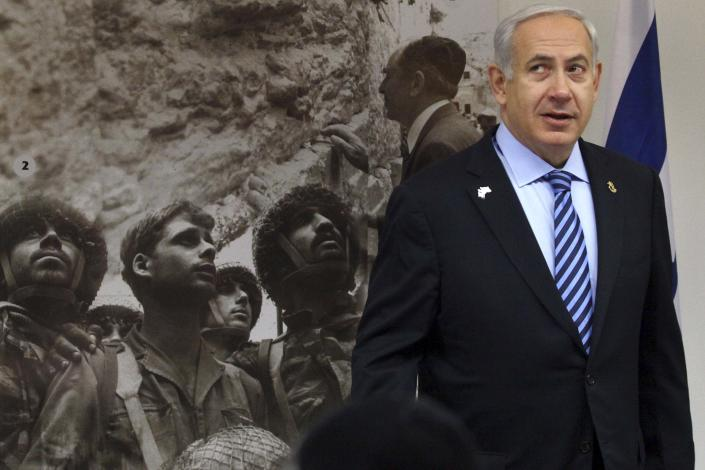 Israeli Prime Minister Benjamin Netanyahu heads a special cabinet meeting marking 'Jerusalem Day' in the Ammunition Hill memorial in Jerusalem, Sunday, May 20, 2012. 'Jeruslem Day' marks the anniversary of Israel's capture of the eastern part of the city in the 1967 Mideast war. Picture in background shows Israeli paratroopers next to the Western Wall in June 1967. (AP Photo/Abir Sultan, Pool)