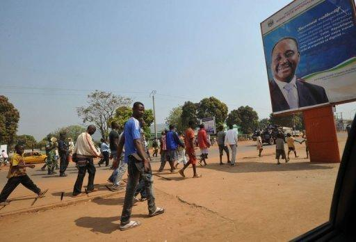 <p>People walk past a poster of the Central African Republic's President Francois Bozize in Bangui on December 28, 2012. The Central African Republic's neighbours took steps Friday to tackle the crisis in the chronically unstable nation, where rebels have advanced towards the capital Bangui, stoking local and international alarm.</p>