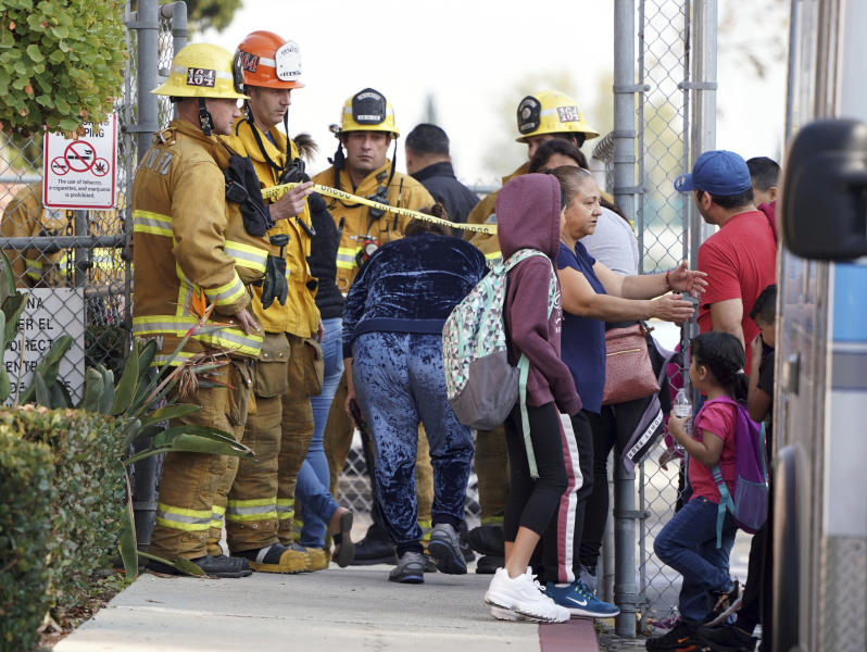 Firefighters allow parents into Park Avenue Elementary School where multiple people were treated for jet fuel exposure in Cudahy, Calif.,  on Tuesday, Jan. 14, 2020. A jet returning to LAX dumped its fuel over the neighborhood and the school. Affected people at the school were treated for skin and eye irritation. No patients were transported to hospitals. (Scott Varley/The Orange County Register via AP)