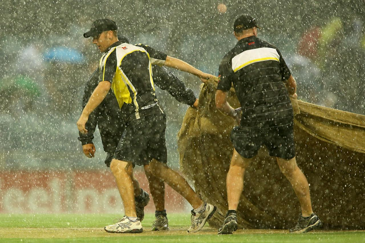 PERTH, AUSTRALIA - DECEMBER 12:  Ground staff place the covers over the wicket area as heavy rain sets in during the Big Bash League match between the Perth Scorchers and the Melbourne Stars at WACA on December 12, 2012 in Perth, Australia.  (Photo by Paul Kane/Getty Images)