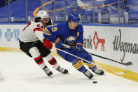 Buffalo Sabres defenseman Jake McCabe (19) and New Jersey Devils forward Miles Wood (44) battle for the puck during the first period of an NHL hockey game Saturday, Jan. 30, 2021, in Buffalo, N.Y. (AP Photo/Jeffrey T. Barnes)