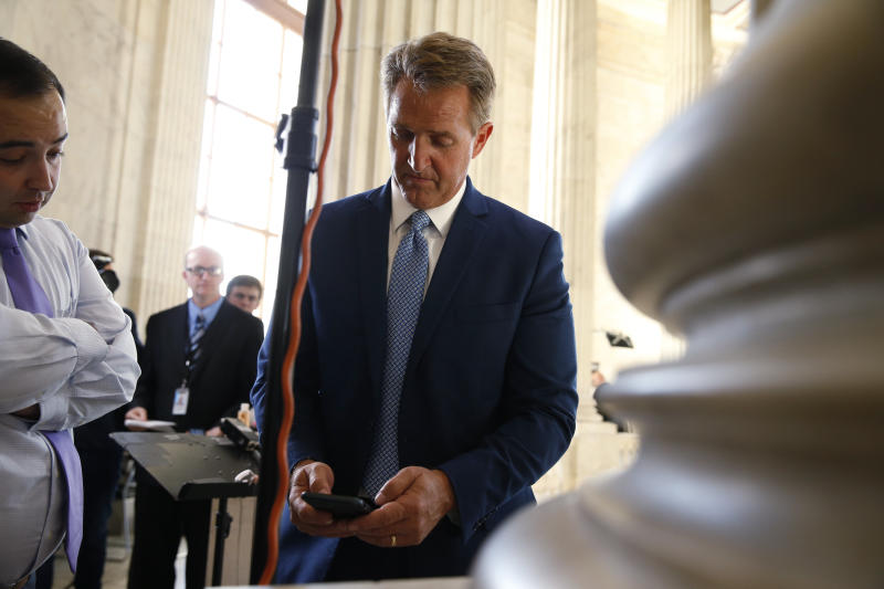 Sen. Jeff Flake (R-Ariz.) pauses to check his phone after announcing he will not run for re-election on Oct. 24, 2017. (Joshua Roberts/Reuters)