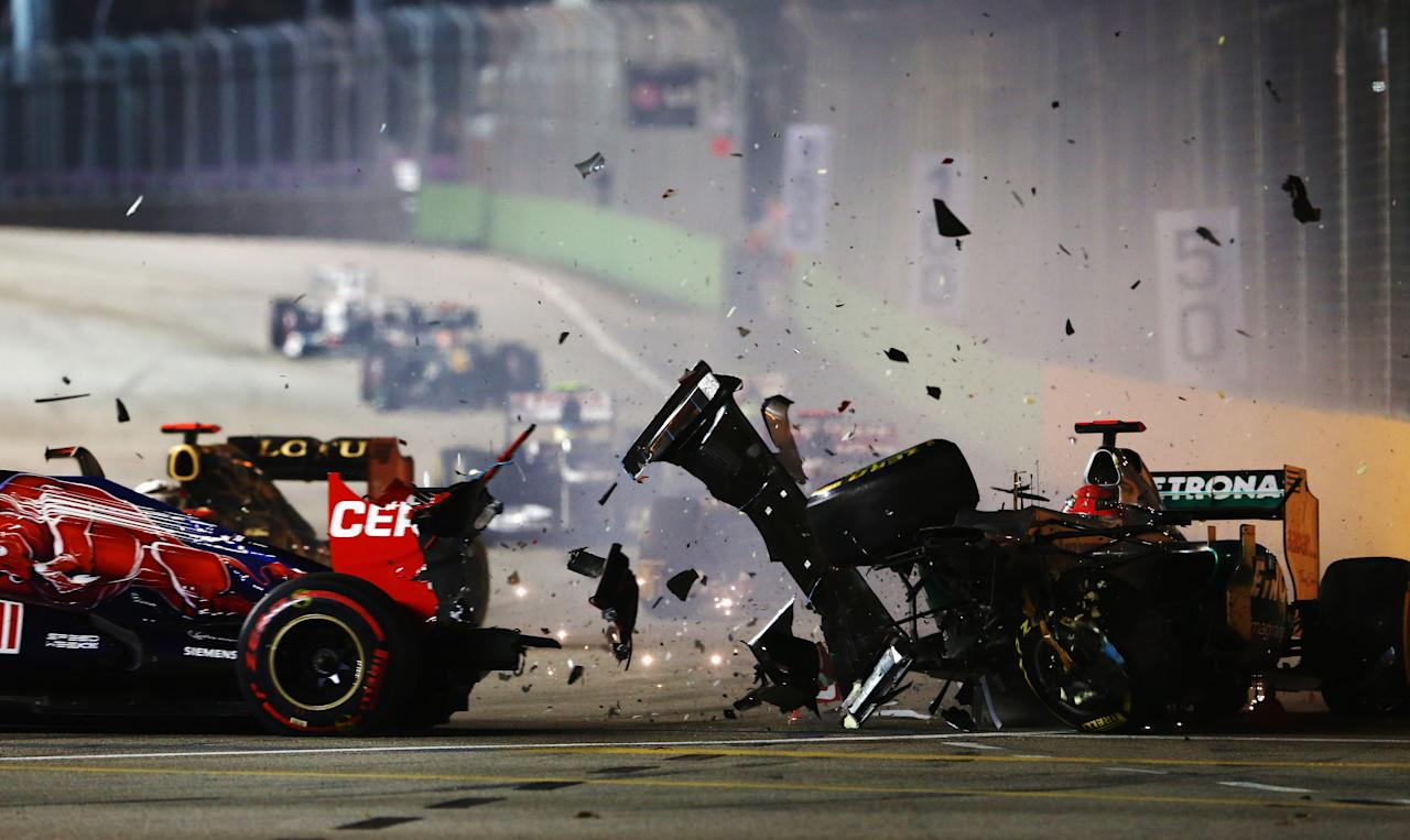 SINGAPORE - SEPTEMBER 23:  Michael Schumacher of Germany and Mercedes GP crashes into the back of Jean-Eric Vergne of France and Scuderia Toro Rosso during the Singapore Formula One Grand Prix at the Marina Bay Street Circuit on September 23, 2012 in Singapore, Singapore.  (Photo by Robert Cianflone/Getty Images)