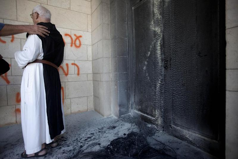 "A catholic priest looks at anti-Christian graffiti written in Hebrew "" at the Latrun Trappist Monastery where Israeli police say vandals overnight have spray-painted anti-Christian and pro-settler graffiti and set the monastery's door on fire, in Latrun, between Jerusalem and Tel Aviv, Israel, Tuesday, Sept 4, 2012. Suspicion fell on Jewish settlers and their supporters who retaliate against anti-settlement measures, generally by attacking Palestinian property, but also by vandalizing Christian sites and Israeli military facilities. Earlier this week, the government ordered settlers out of two unauthorized enclaves in the West Bank. Some of the graffiti referred to unauthorized settler outposts and one read, ""Jesus is a monkey."" (AP Photo/Oded Balilty)"
