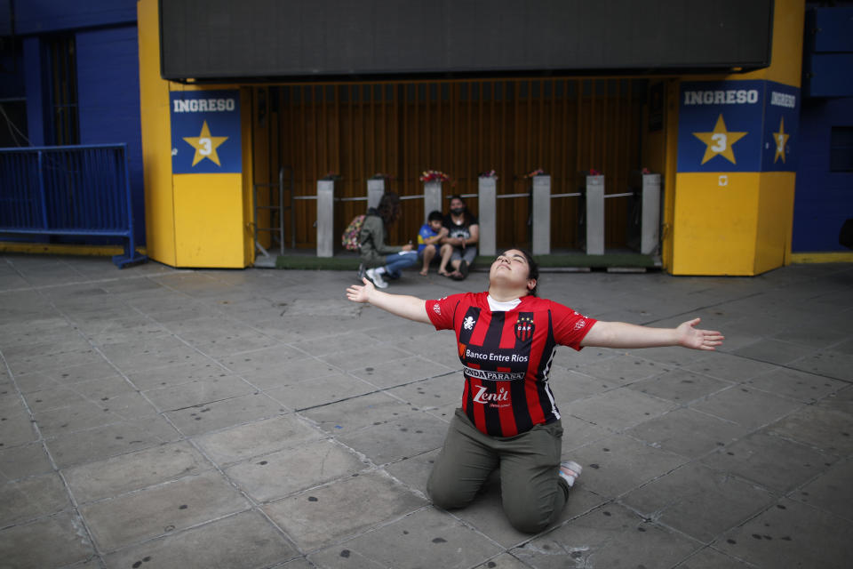 A fan mourns the death of Diego Maradona, as she kneels at the entrance of the Boca Juniors stadium known as La Bombomera, in Buenos Aires, Argentina, Wednesday, Nov. 25, 2020. The Argentine soccer great who was among the best players ever and who led his country to the 1986 World Cup title before later struggling with cocaine use and obesity, died from a heart attack on Wednesday at his home in Buenos Aires. He was 60. (AP Photo/Natacha Pisarenko)