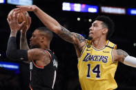 Portland Trail Blazers guard Damian Lillard, left, looks to pass while moving to the basket and defended by Los Angeles Lakers guard Danny Green during the first half of an NBA basketball game in Los Angeles, Friday, Jan. 31, 2020. (AP Photo/Kelvin Kuo)
