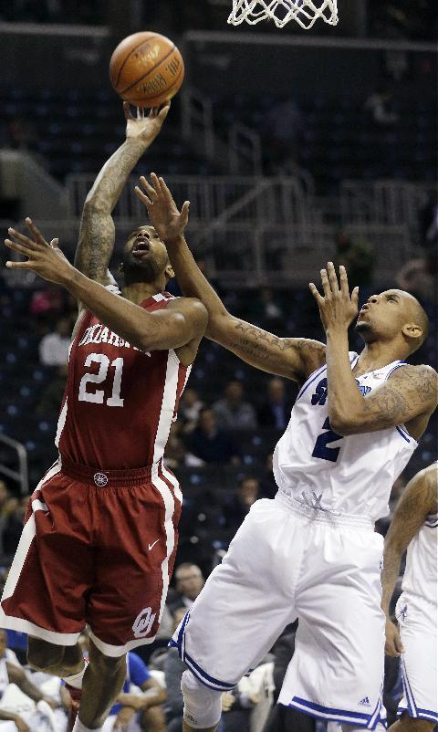 Oklahoma Sooners Cameron Clark (21) shoots over Seton Hall Brandon Mobley during the first half of a Coaches vs. Cancer NCAA college basketball game Friday, Nov. 22, 2013, in New York. Oklahoma won 86-85. (AP Photo/Frank Franklin II)