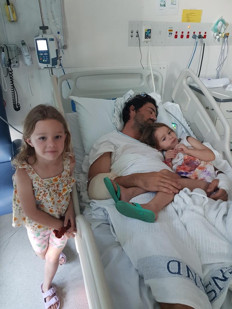 Mr Turner is seen in hospital with one daughter laying in his bed and the other standing next to him. Source: Turner family