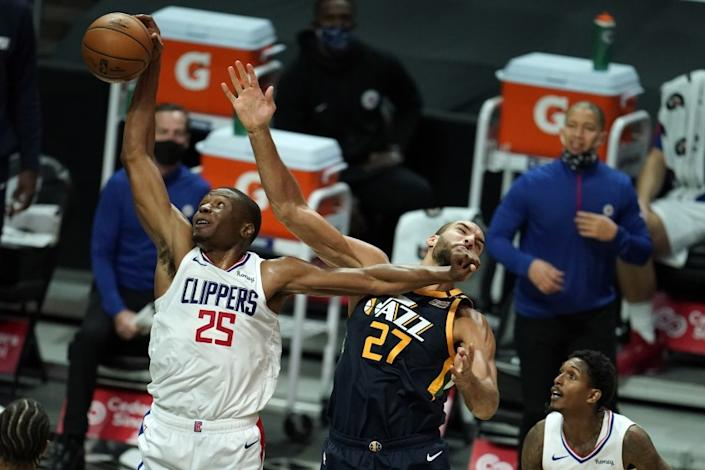 Los Angeles Clippers forward Mfiondu Kabengele (25) shoots over Utah Jazz center Rudy Gobert (27) during the first half of an NBA preseason basketball game Thursday, Dec. 17, 2020, in Los Angeles. (AP Photo/Marcio Jose Sanchez)