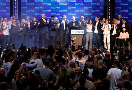 Blue and White party leader Benny Gantz and party co-leaders Yair Lapid, Moshe Yaalon and Gaby Ashkenazi react at the party's headquarters following the announcement of exit polls during Israel's parliamentary election in Tel Aviv