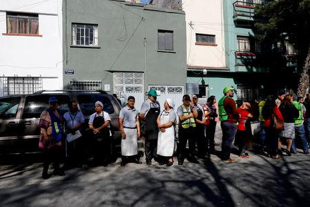 Workers are seen at a street following an earthquake in Mexico City, Mexico February 1, 2019. REUTERS/Carlos Jasso