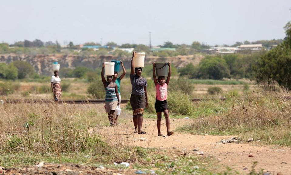 Bulawayo residents carry water home from a borehole in the township of Luveve.
