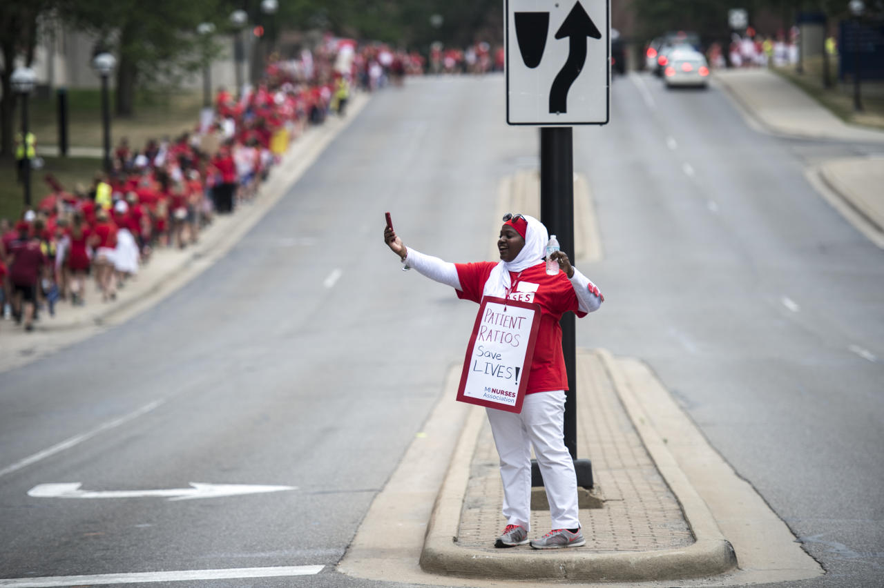 Tasneem Abdul-Basir, a labor and delivery nurse since 2001, takes pictures of fellow rally members on E Medical Center Drive during an informational picket and rally in support of the University of Michigan Professional Nurses Council in Ann Arbor on Saturday, July 14, 2018. Participants in the rally continue their fight with Michigan Medicine over the contract which expired on June 30. The picket was held to protest contentious issues such as retirement cutbacks, increased health care costs and guaranteed staffing levels remain unresolved. (Ben Allan Smith/Ann Arbor News via AP)