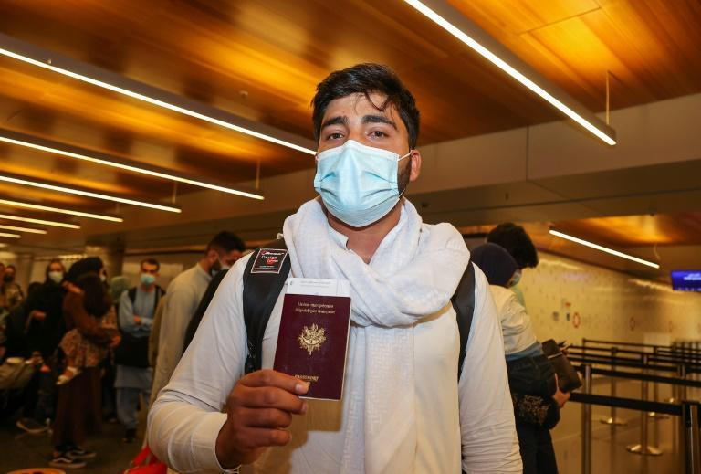 One of the 49 French nationals evacuated from Afghanistan on Friday, September 10, 2021, showed is passport on arrival in the Qatari capital Doha (AFP/KARIM JAAFAR)