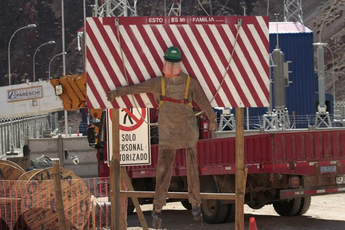"""This May 23, 2013 photo, shows lettering that reads in Spanish; """"This is my family,"""" above an effigy of a worker, at the entrance of the Barrick Gold Corp's Pascua-Lama project facilites in northern Chile. Chile's newly empowered environmental regulator confirmed nearly two-dozen violations of Barrick's environmental impact agreement on Friday, May 24, 2013, blocking all other construction on the $8.5 billion project until the Canadian company keeps its promises to prevent water contamination. (AP Photo/Jorge Saenz)"""