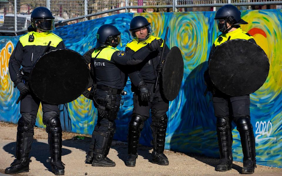 Dutch riot police, in front of a mural on a halfpipe inspired by Van Gogh, wait to break up the demonstration - AP Photo/Peter Dejong
