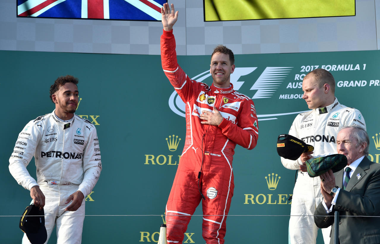 Sebastian Vettel celebrates his victory on the podium alongside Lewis Hamilton (left) and Valtteri Bottas (AFP Photo/SAEED KHAN)