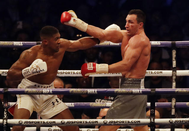 FILE - In this Saturday, April 29, 2017 file photo, British boxer Anthony Joshua, left, fights Ukrainian boxer Wladimir Klitschko for Joshua's IBF and the vacant WBA Super World and IBO heavyweight titles at Wembley stadium in London. Joshua won with an 11th round stoppage. Former heavyweight boxing champion turned philanthropist and management thinker Wladimir Klitschko praises his home country of Ukraine in a year when it has had a starring role in politics and on television in the United States. (AP Photo/Matt Dunham, File)