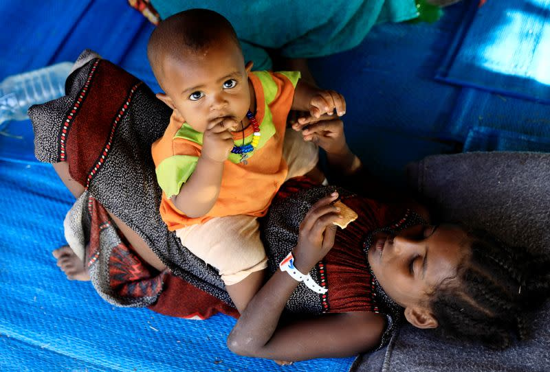 An Ethiopian woman who fled war in Tigray region, is seen with her child inside a makeshift shelter at the Um-Rakoba camp on the Sudan-Ethiopia border in Al-Qadarif state