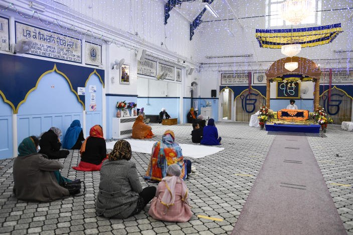 FILE - In this Sunday, March 21, 2021 file photo, people pray at the Guru Nanak Gurdwara Sikh temple, on the day the first Vaisakhi Vaccine Clinic is launched, in Luton, England. Thanks to an efficient vaccine roll out program and high uptake rates, Britain is finally saying goodbye to months of tough lockdown restrictions. From Monday May 17, 2021, all restaurants and bars can fully reopen, as can hotels, cinemas, theatres and museums, and for the first time since March 2020, Britons can hug friends and family and meet up inside other people's houses. (AP Photo/Alberto Pezzali, File)