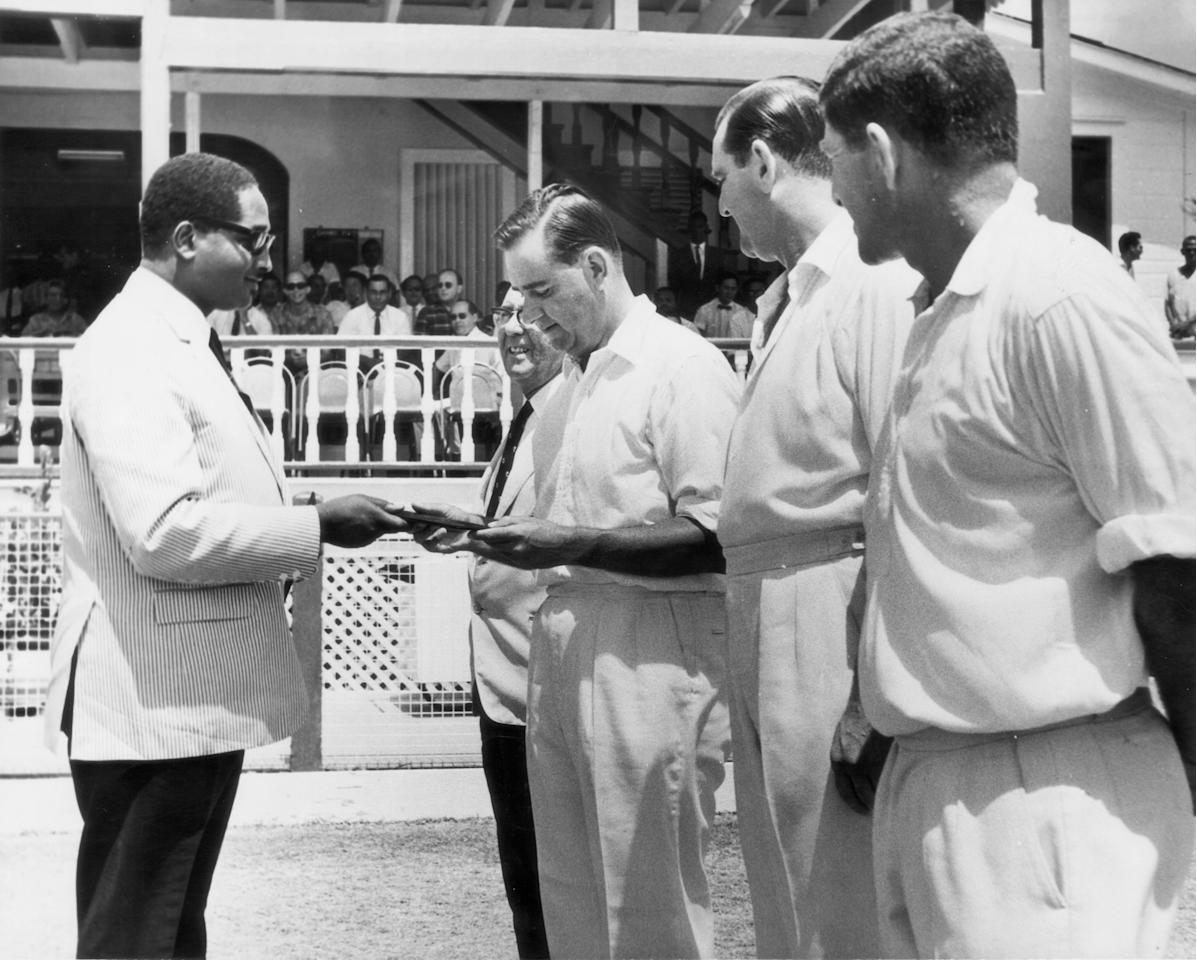 At the start of the fifth and final West Indies/MCC test at Georgetown Guyana, Guyanan Prime Minister Forbes Burnham (1923 - 1885) presents England cricket captain Colin Cowdrey with a set of stamps commmemorating the test series, 1st April 1968. Ken Barrington (1930 - 1981) (Photo by Central Press/Hulton Archive/Getty Images)