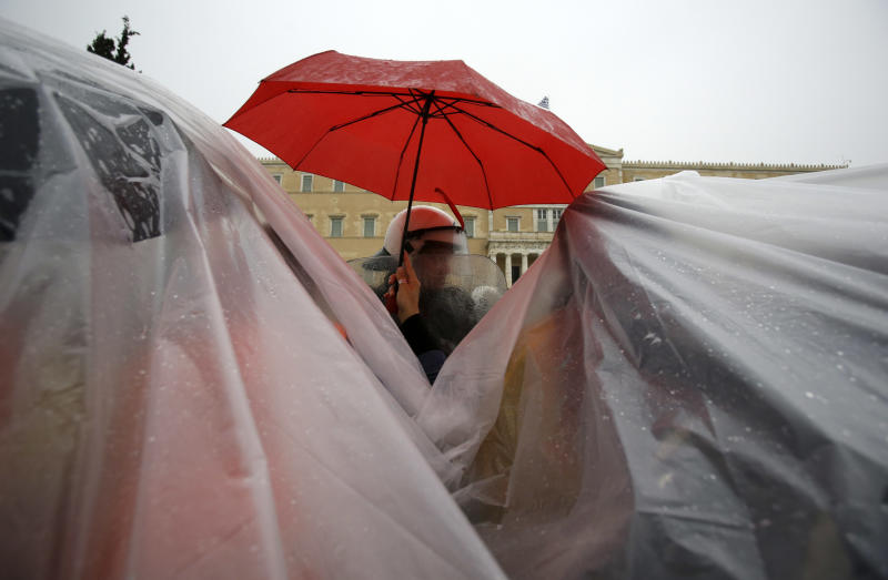 A protesting school security worker holds an umbrella over a riot policeman as her colleagues take cover under a plastic sheet during a rally in front of the Greek Parliament in Athens, Wednesday, Nov. 6, 2013. Services across Greece shut down Wednesday as unions held a 24-hour general strike to protest further austerity cuts in the cash-strapped country. (AP Photo/Thanassis Stavrakis)