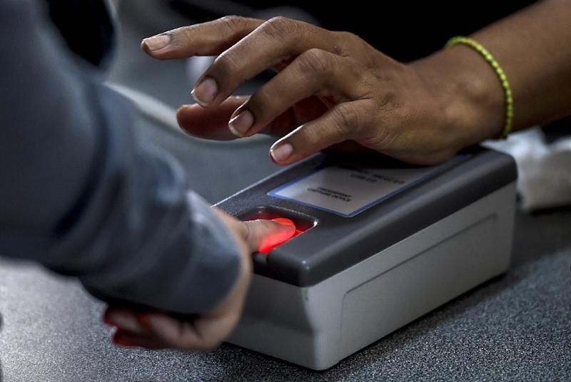 A woman presses a finger on a scanner during the authentication procedure of her signature for a recall referendum, in Caracas on June 24, 2016 (AFP Photo/Juan Barreto)