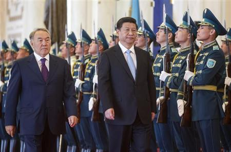 Kazakhstan's President Nazarbayev and his Chinese counterpart Xi walk past honor guards during an official welcoming ceremony in Astana