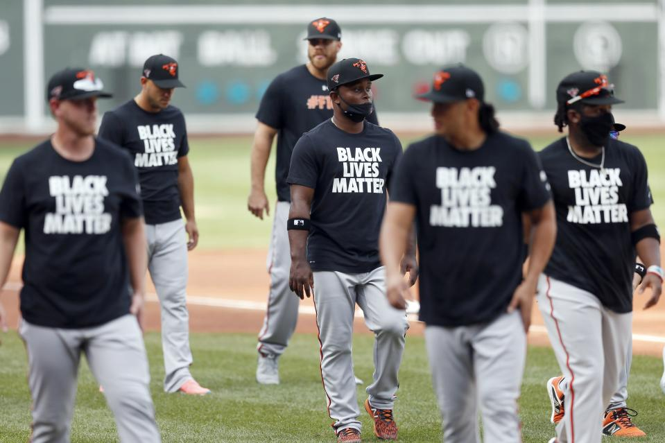Baltimore Orioles players warm up in Black Lives Matter shirts before an opening day baseball game against the Boston Red Sox at Fenway Park, Friday, July 24, 2020, in Boston. (AP Photo/Michael Dwyer)