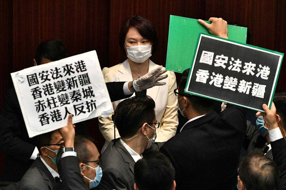 Hong Kong pro-democracy lawmakers holding up placards are blocked by security as they protest during a House Committee meeting, chaired by pro-Beijing lawmaker Starry Lee (top C-in white jacket), concerning the second reading of a national anthem bill, at the Legislative Council in Hong Kong on May 22, 2020. - A proposal to enact new Hong Kong security legislation was submitted to China's rubber-stamp on May 22, state media said, a move expected to fan fresh protests in the semi-autonomous financial hub. (Photo by Anthony WALLACE / AFP) (Photo by ANTHONY WALLACE/AFP via Getty Images)