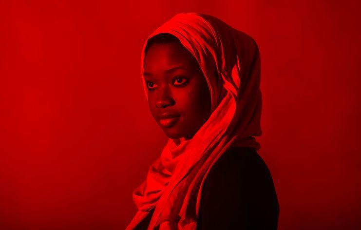 Woman wearing hijab looking away against red background