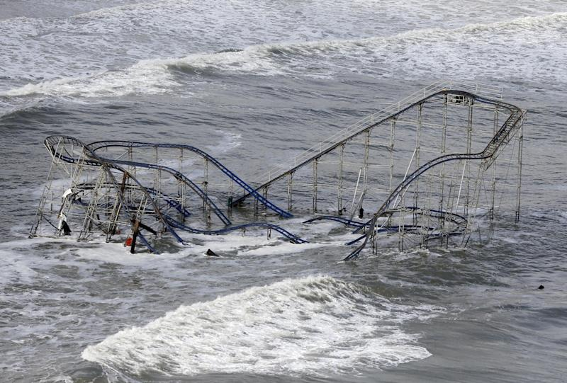 "FILE - In this Wednesday, Oct. 31, 2012 file photo, waves wash over a roller coaster from a Seaside Heights, N.J. amusement park that fell in the Atlantic Ocean during superstorm Sandy. Though it's tricky to link a single weather event to climate change, Hurricane Sandy was ""probably not a coincidence"" but an example of extreme weather events that are likely to strike the US more often as the world gets warmer, the U.N. climate panel's No. 2 scientist told the Associated Press Tuesday, Nov. 27, 2012.(AP Photo/Mike Groll, File)"