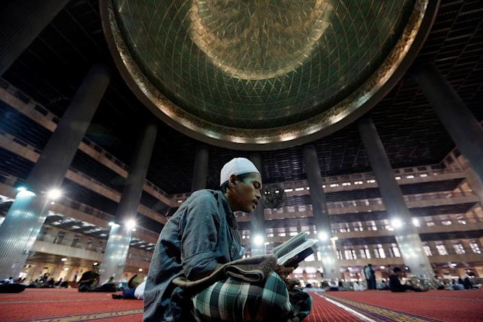 A Muslim man reads the Koran while waiting for the Iftar (breaking fast) meal during the last week of the holy fasting month of Ramadan at Istiqlal Mosque in Jakarta, Indonesia June 20, 2017. REUTERS/Agoes Rudianto