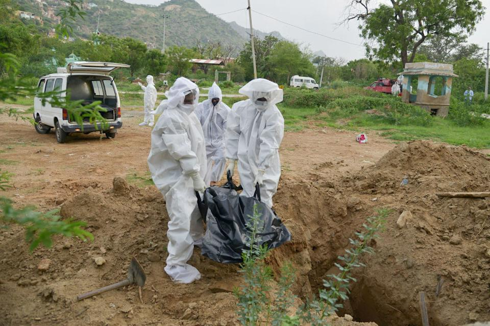 Health workers wearing protective suits buried the body of a man who died from COVID-19 at a graveyard in Ajmer, Rajasthan. Source: Getty