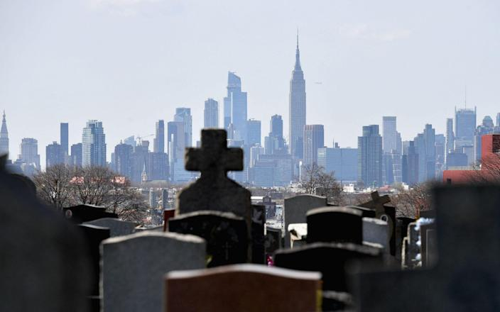 file photo taken on April 07, 2020 gravestones from Linden Hill Methodist Cemetery are seen with the Manhattan skyline in the background in Brooklyn, New York. - The US death toll from the Covid-19 pandemic surpassed 600,000 on June 15, 2021, according to figures from Johns Hopkins University, - AFP