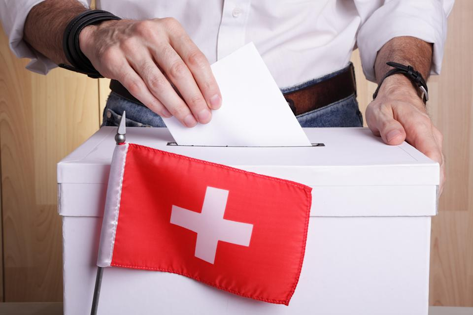 Unrecognizable citizen casting his vote. The Swiss flag is in front of the polling box with