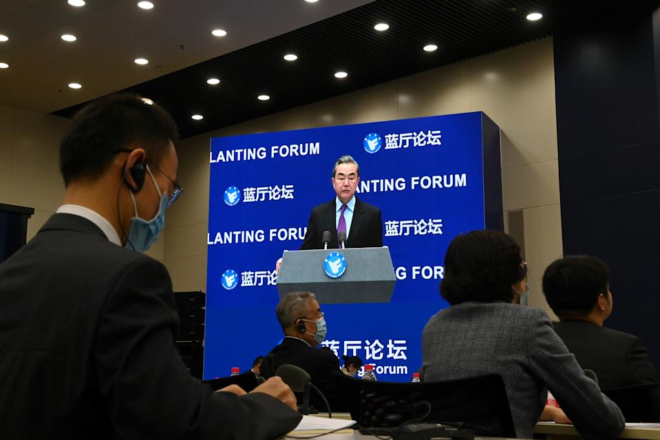 Chinese Foreign Minister Wang Yi is seen on a screen as he speaks at the Lanting Forum on China-US relations in Beijing on February 22, 2021. (Photo by GREG BAKER / AFP) (Photo by GREG BAKER/AFP via Getty Images)