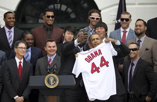 "Boston Red Sox designated hitter David ""Big Papi"" Ortiz takes a selfie with President Barack Obama, holding a Boston Red Sox jersey presented to the president, on the South Lawn of the White House in Washington, Tuesday, April 1, 2014, during a ceremony where the president honored the 2013 World Series baseball champion Boston Red Sox. From left are, principal owner John W. Henry, Executive Vice President - General Manager Ben Cherington, pitchers Junichi Tazawa, Ortiz, the president, and pitcher Koji Uehara. Top left is infielder Xander Bogaerts. (AP Photo/Carolyn Kaster)"