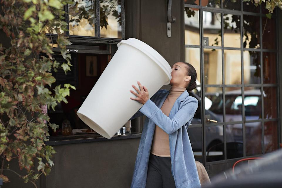 Young woman drinking coffee from large disposable cup at coffee takeout counter