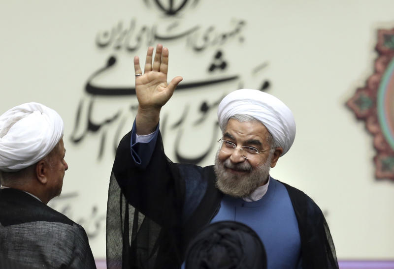 """Iran's new President Hasan Rouhani, waves after swearing in at the parliament, in Tehran, Iran, Sunday, Aug. 4, 2013. Iran's new president on Sunday called on the West to abandon the """"language of sanctions"""" in dealing with his country over its contentious nuclear program, hoping to ease the economic pressures now grinding its people. Rouhani spoke after being sworn in as president in an open session of parliament Sunday, capping a weekend that saw him endorsed by Ayatollah Ali Khamenei, Iran's supreme leader. (AP Photo/Ebrahim Noroozi)"""