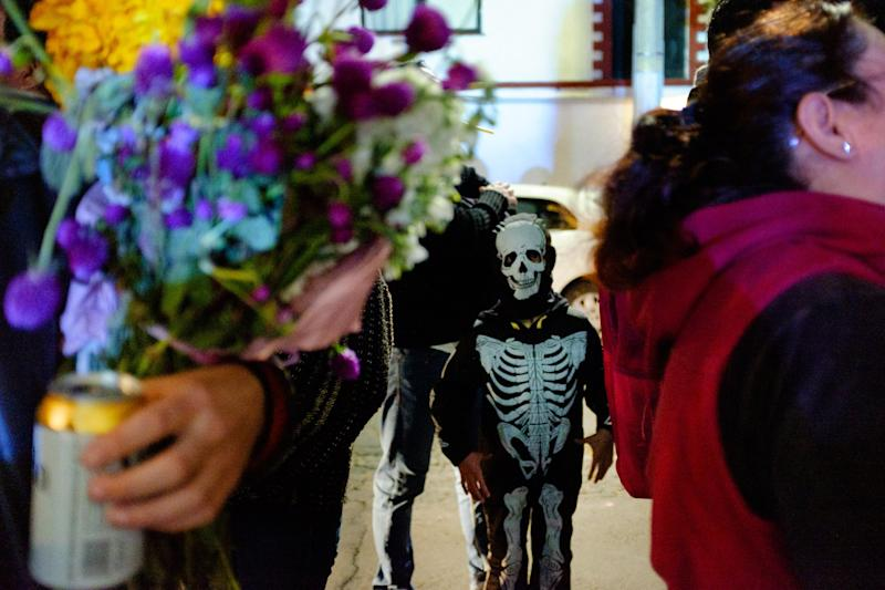 A young reveler in a skeleton costume.