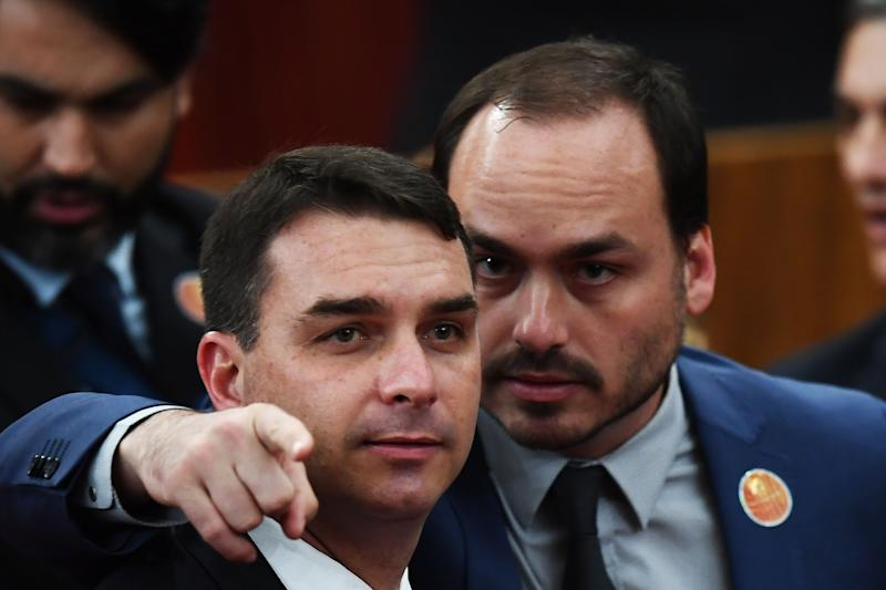 Brazilian Senator for Rio de Janeiro Flavio Bolsonaro (L) and Councillor of Rio de Janeiro Carlos Bolsonaro attend their father Brazilian President-elect Jair Bolsonaro's ceremony to receive a diploma that certifies he can take office as president, at the TSE in Brasilia, on December 10, 2018. - Bolsonaro takes office on January 1, 2019. (Photo by EVARISTO SA / AFP) (Photo credit should read EVARISTO SA/AFP via Getty Images)