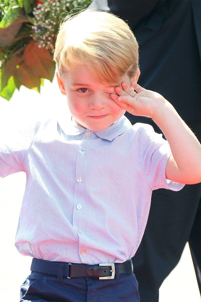 <p>Prince George cracks a smile even though he seems to be waking up from a plane nap...</p>