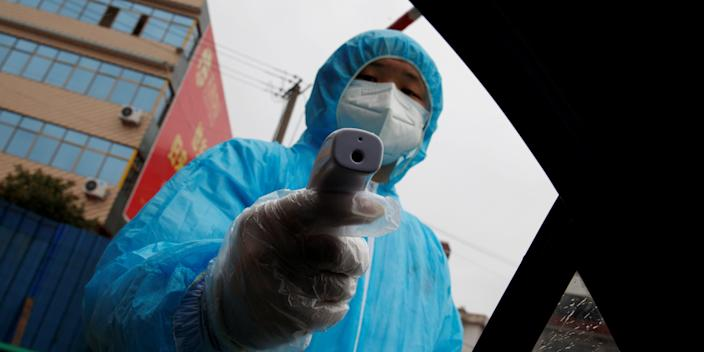 A medical worker holds a thermometer to check a passenger's temperature at a checkpoint in Anhui province, China.