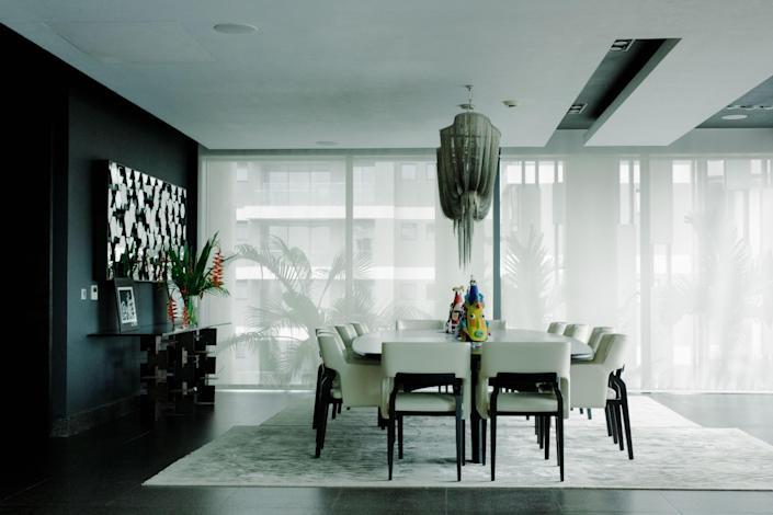 A Terzani chandelier hangs above a custom dining table and chairs by Caste Design.