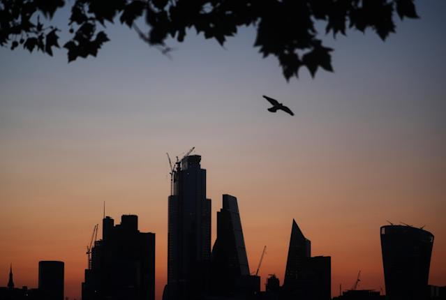 A bird flies as the sun rises behind the city of London financial district in London. (Hannah McKay/Reuters)