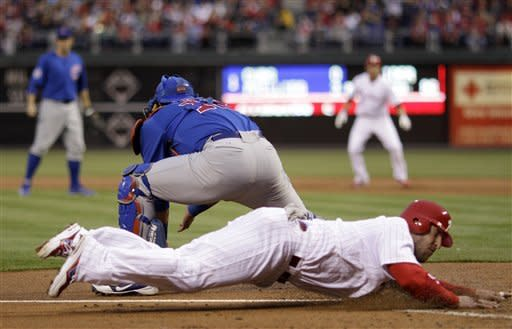 Philadelphia Phillies' Laynce Nix, bottom, slides home to score as Chicago Cubs catcher Geovany Soto waits for the throw on a hit by Pete Orr in the first inning of a baseball game, Monday, April 30, 2012, in Philadelphia. (AP Photo/Matt Slocum)